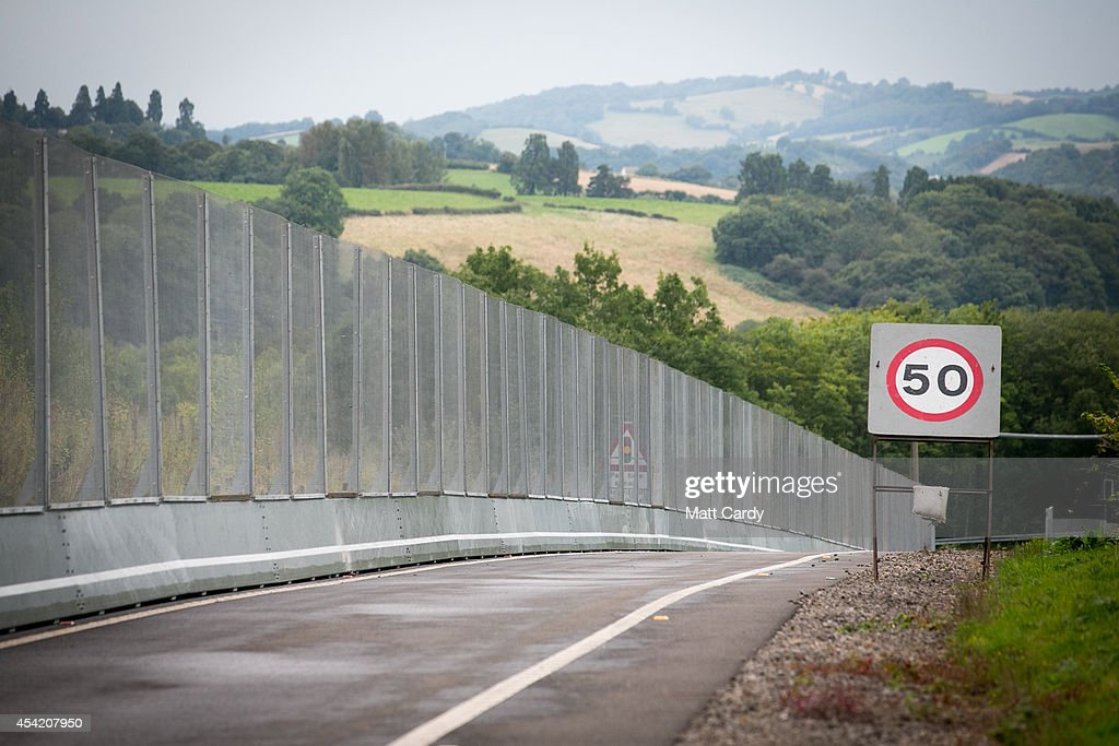 Vehicles pass beside the security fence that has been erected for several miles around the Celtic Manor Resort ahead of the Nato Summit 2014 that is being held in South Wales next week on August 26, 2014 in Cardiff, Wales. The barriers have been erected as a security measure as preparations for the international conference continue at the Celtic Manor Resort in Newport.