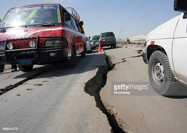 Vehicles pass by a cracked portion of the Pan American highway after an earthquake hit the area in Pisco Peru Friday Aug 17 2007 Peru's government...