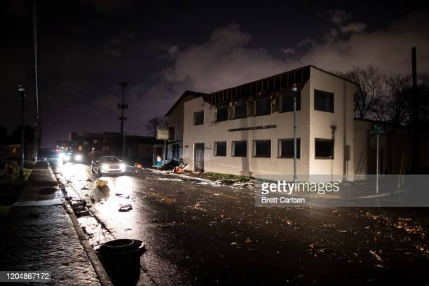 Vehicles pass by damaged buildings on Jefferson St after a tornado passed through the area on March 3 2020 in Nashville Tennessee A tornado passed...