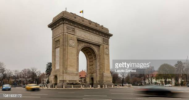 Vehicles pass by the Arcul de Triumf on December 7, 2018 in Bucharest, Romania. The Arch Of Triumph was built in 1922 to the memory of winning Word...