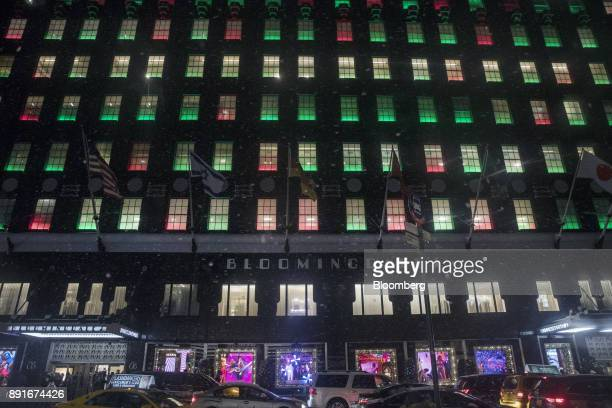 Vehicles pass in front of the holiday decorations on display at the Bloomingdale's Inc department store in New York US on Saturday Dec 9 2017...