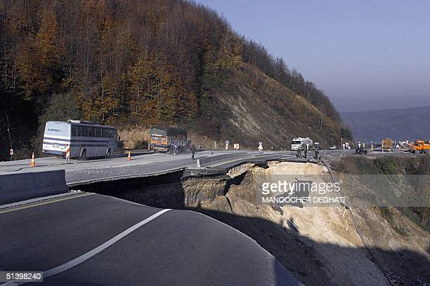 Vehicles pass over a damaged motorway between Duzce in Bolu in northwestern Turkey 14 November 1999 after an earthquake measuring 72 on the openended...