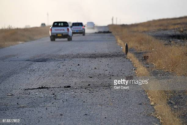 Vehicles pass unexploded IED's left by ISIS on the road from Erbil to Mosul on October 18 2016 near Mosul in Iraq Joint forces from countries...