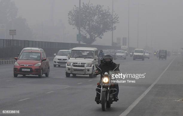 Vehicles plying with light at DelhiGurgaon expressway due to poor visibility on December 7 2016 in Gurgaon India Fog over parts of north India...
