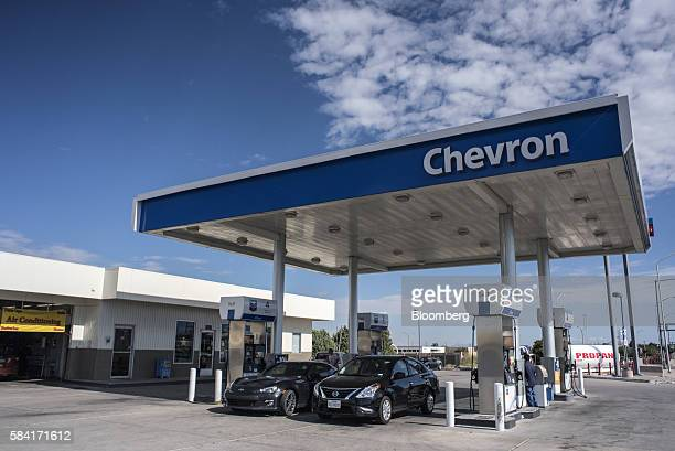 Vehicles refuel at a Chevron Corp gas station in Albuquerque New Mexico US on Tuesday July 26 2016 Chevron is scheduled to release earnings figures...