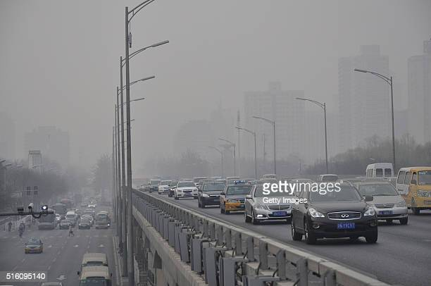 Vehicles run in the smog on March 17 2016 in Beijing China The Air Quality Index of Beijing reached 357 on Thursday and Beijing had sounded the...