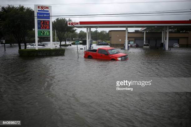Vehicles sit abanoned at an Exxon Mobil Corp gas station due to floodwaters from Hurricane Harvey in Houston Texas US on Tuesday Aug 29 2017...
