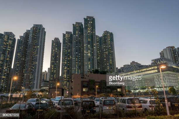Vehicles sit at a car park in front of illuminated residential buildings at the Metro Town development jointly developed by CK Asset Property...