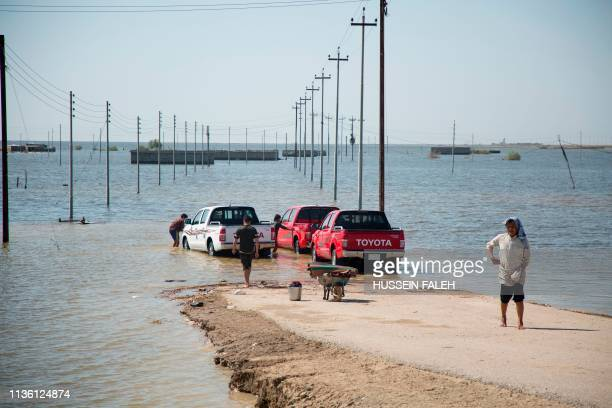 Vehicles sit at the edge of a flooded area in southern Iraq's al-Qurna district, north of Basra, on April 10, 2019. - Weeks of rain -- compounded by...
