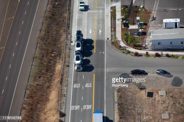 Vehicles sit on a car transporter truck outside of the Tesla Inc assembly plant in this aerial photograph taken above Fremont California US on...