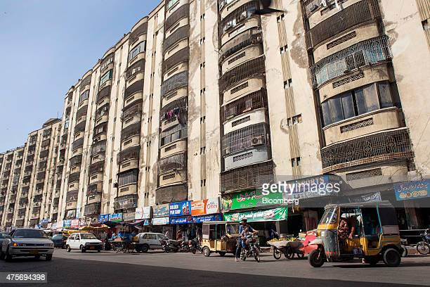 Vehicles sit outside stores on the ground floor of a residential building in Karachi Pakistan on Friday May 29 2015 Pakistan's budget is scheduled to...
