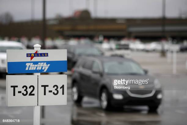 Vehicles sit parked as Dollar Thrifty Automotive Group Inc signage is displayed at a rental location inside the Louisville International Airport in...