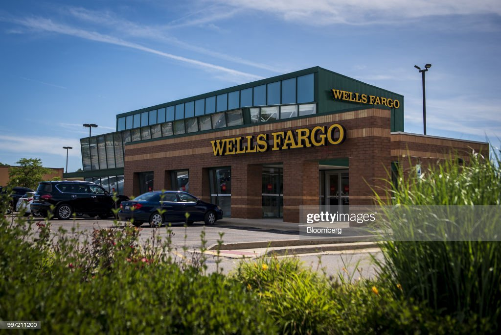 Vehicles sit parked outside a Wells Fargo & Co. bank branch in Palatine, Illinois, U.S., on Tuesday, July 10, 2018. Wells Fargo & Co. is scheduled to release earnings figures on July 13. Photographer: Christopher Dilts/Bloomberg via Getty Images