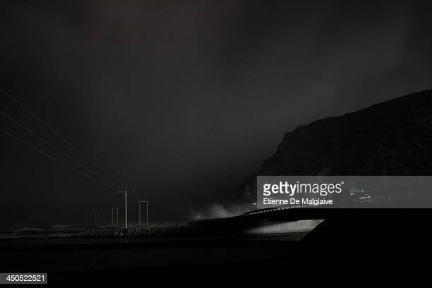 Vehicles speed through a dark fallout of ashes spewed by Eyjafjallajokull after the fallout completely blacked out visibility under the plume on May...