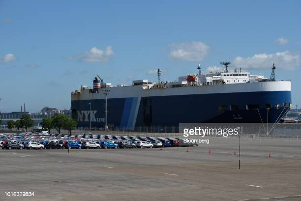 Vehicles stand as the Nippon Yusen KK Hojin vehicle carrier sits berthed at the Nagoya Port in Nagoya Japan on Tuesday July 31 2018 Japan is...