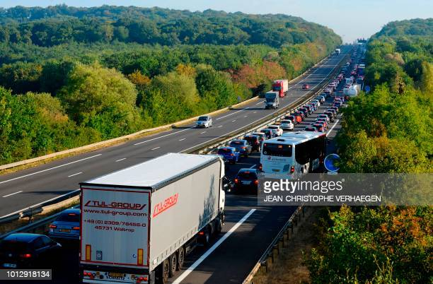 Vehicles stand in a traffic jam near the FranceLuxembourg border in Zoufftgen eastern France on early August 2 as people are on their way to work...
