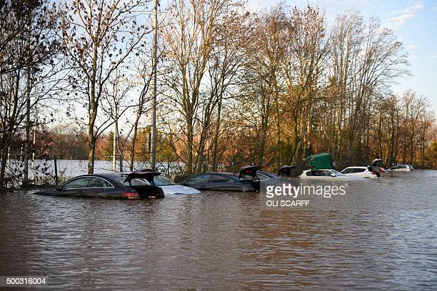 Vehicles stand submerged in flood waters one with an industrial waste bin on its roof in the car park of Carlisle United Football Club in Carlisle...