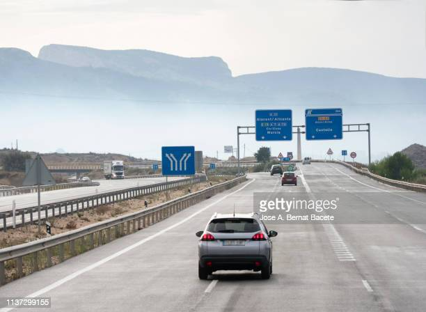 vehicles that move in a highway of several rails during a rainy day in the morning. highway a 7 - e 15, spain, europe - valencia spain stock pictures, royalty-free photos & images