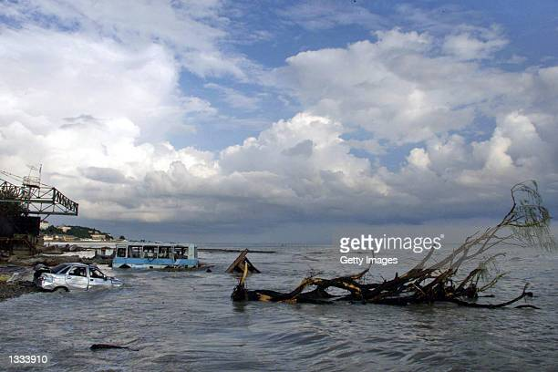 Vehicles that were swept away by rising waters into the Black Sea lie half sunk August 09 2002 in Shirokaya Balka Russia Rescue workers battled...