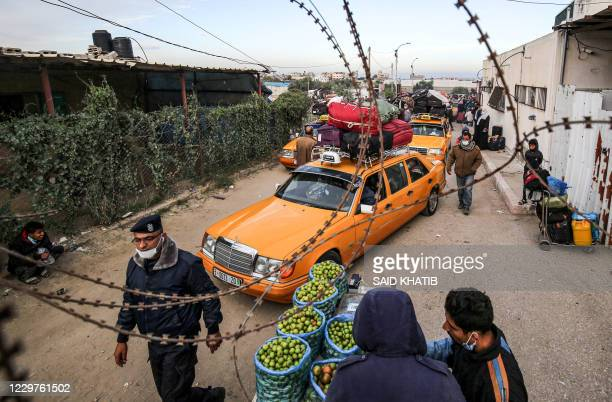 TOPSHOT Vehicles transporting Palestinians about to cross onto the Egyptian side wait at the Rafah border crossing between the Gaza Strip and Egypt...