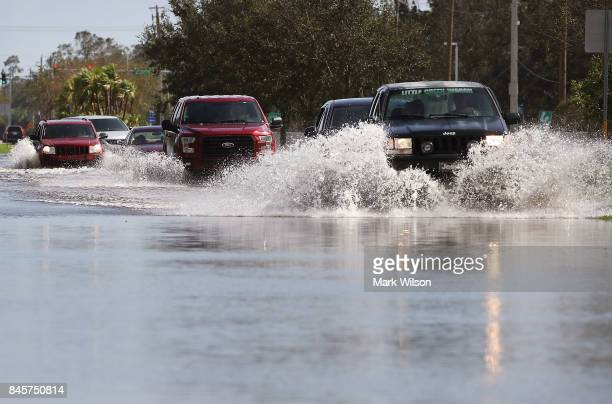 Vehicles travel along a road flooded by Hurricane Irma on September 11 2017 in Estero Florida Hurricane Irma made landfall in the Florida Keys as a...