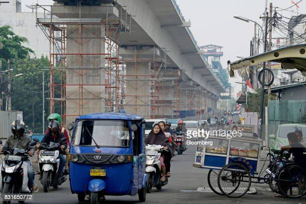 Vehicles travel past an elevated track for the Jakarta Mass Rapid Transit as it stands under construction in Jakarta Indonesia on Sunday Aug 13 2017...