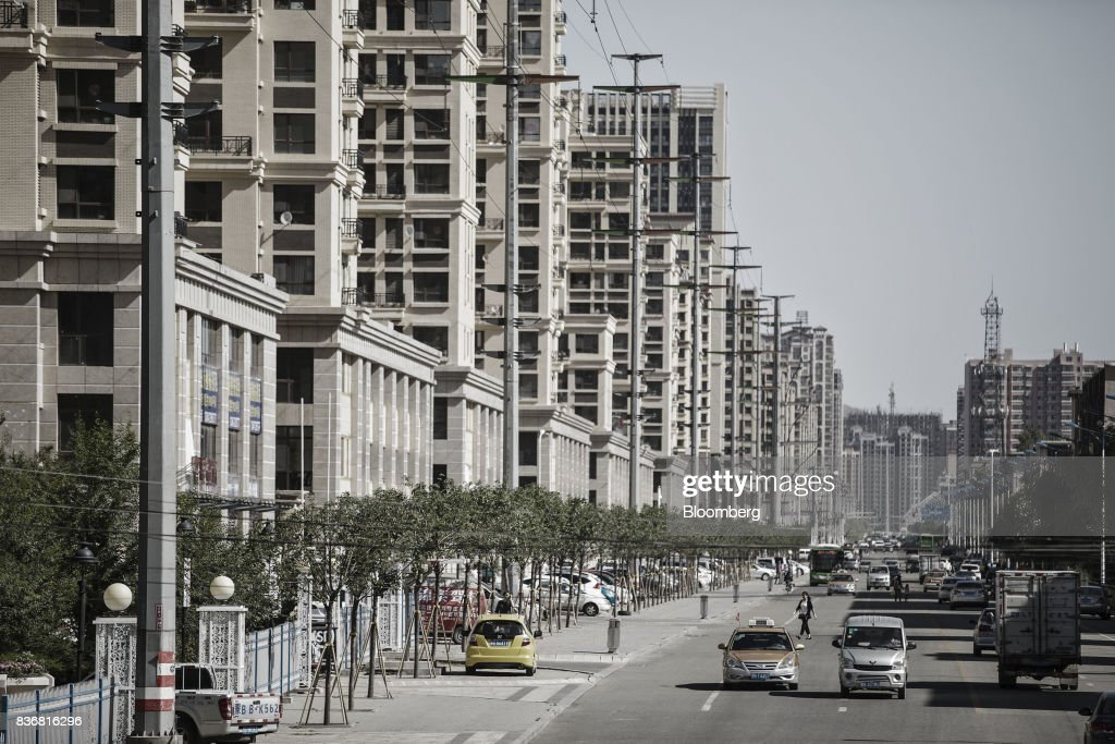 Vehicles travel past new residential buildings in Baotou, Inner Mongolia, China, on Friday, Aug. 11, 2017. China's economy showed further signs of entering a second-half slowdown, as curbs on property, excess borrowing and industrial overcapacity began to bite. Photographer: Qilai Shen/Bloomberg via Getty Images