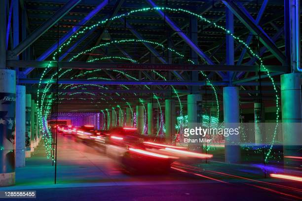 Vehicles travel through a tunnel of lights under the stands during the opening night of the Glittering Lights drive-thru light show at the Las Vegas...