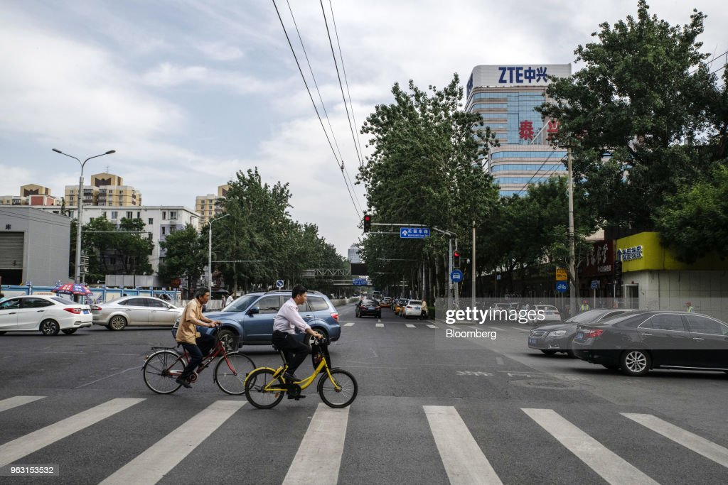 Vehicles travel through an intersection near a ZTE Corp. building in Beijing, China, on Thursday, May 24, 2018. PresidentDonald Trumpsaid the U.S. would allow Chinese telecommunications-equipment maker ZTE Corp. to remain in business after paying a $1.3 billion fine, changing its management and board and providing 'high-level security guarantees.' Photographer: Gilles Sabrie/Bloomberg via Getty Images