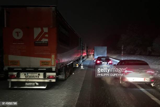 Vehicles travel through fresh snowfall on the A1 autoroute near Senlis in the Oise Department some 30kms northeast of Paris on February 6 2018 / AFP...
