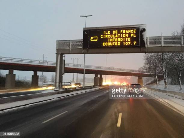 Vehicles travel through fresh snowfall under a traffic information sign which reads that trucks are prohibited and advises to listen to local radio...