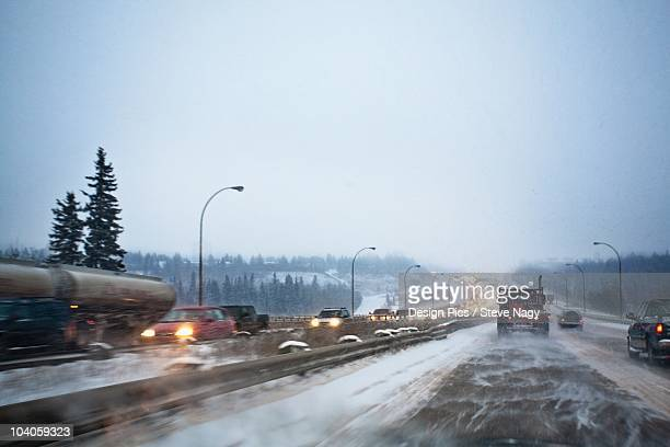 vehicles traveling on the road with snow blowing in winter - edmonton stock pictures, royalty-free photos & images