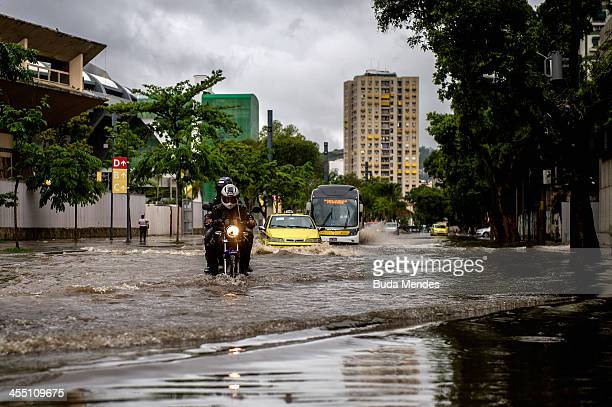 Vehicles try to cross the Professor Eurico Rabelo street in front the Maracana stadium after heavy rains flooded the area on December 11 2013 in Rio...