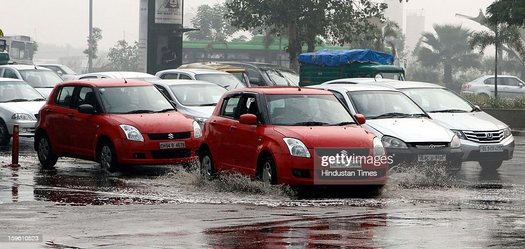 Vehicles wade through a waterlogged road after sudden rain at NH 24 - Ring Road T-point on January 17, 2013 in New Delhi, India. Capital witnessed light rain and chilly winds even though temperatures were above average.