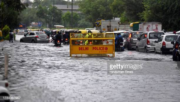 Vehicles wade through a waterlogged stretch at NH24 during heavy rain on July 19, 2021 in New Delhi, India. Rains lashed Delhi NCR for the second...