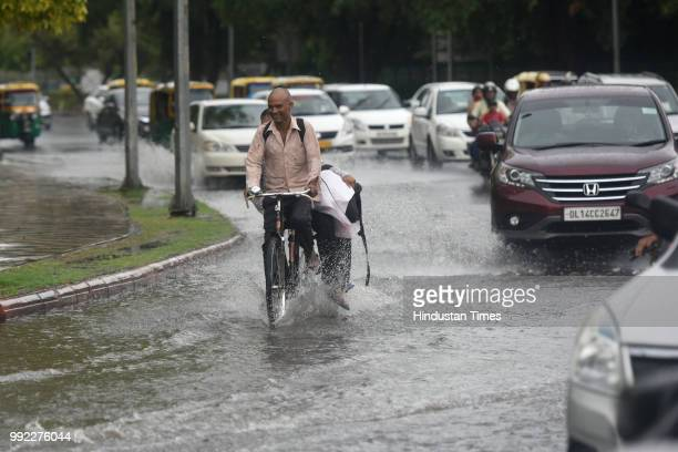 Vehicles wade through water logged road at India Gate circle after heavy monsoon rains lashed New Delhi India on Thursday July 5 2018