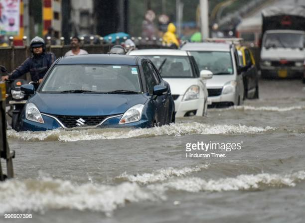 Vehicles wades through a water logged street as it rains at King Circle on July 11 2018 in Mumbai India Heavy rains made a comeback in Mumbai causing...