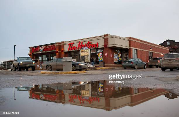 Vehicles wait in line at a Tim Hortons Inc restaurant drivethru in downtown Fort McMurray Alberta Canada on Saturday March 30 2013 The economy of...