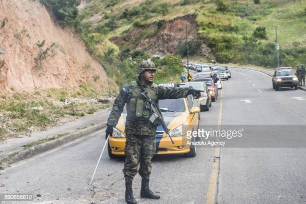 Vehicles wait on a line as Honduran security forces clear a road which was blocked by supporters of the opposition political party 'Alianza' due to...