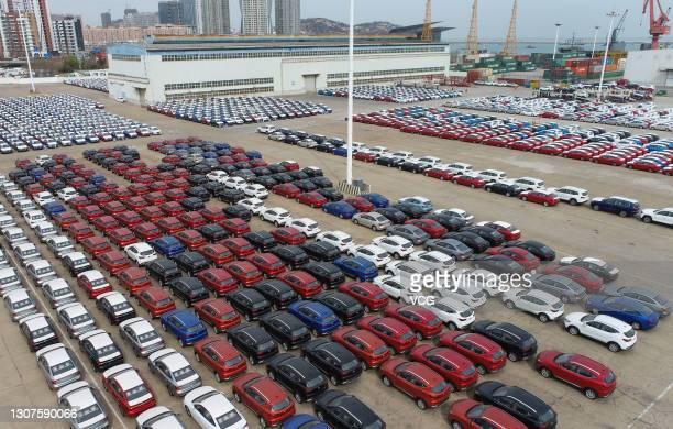 Vehicles which will be shipped abroad sit parked next to a roll-on-roll-off ship at Lianyungang Port on March 17, 2021 in Lianyungang, Jiangsu...