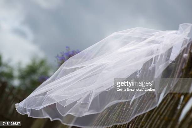 veil on wooden fence against cloudy sky - wedding veil stock photos and pictures