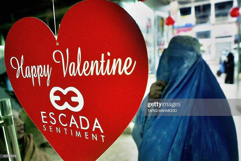 A Veil Clad Pakistani Woman Walks Past A Gift Shop Displaying