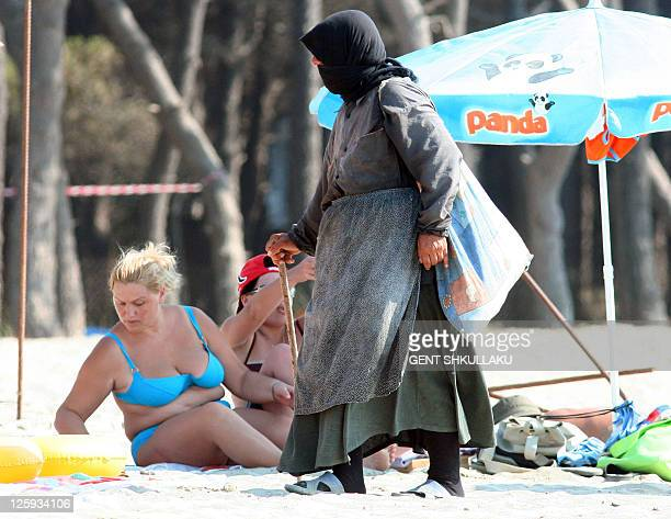 MEMA A veiled albanian woman walks past women wearing bikini swimsuits on a beach in Spille southwest of Tirana on August 2 2011 Bikini's and hijabs...