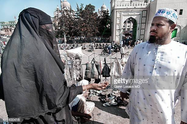 Veiled beggar Muslim man stares at woman Jama Masjid Hyderabhad India Friday prayer Jummha