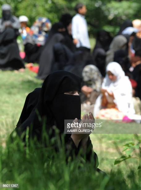 Veiled female follower of newly-released Red Mosque chief cleric Maulana Abdul Aziz prays outside the mosque as Aziz leads Friday prayers in...