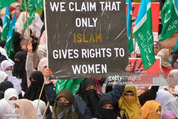Veiled female supporters of Pakistani Islamic political party Jamaat-e-Islami carry placards and banners as they march during a rally to mark the...
