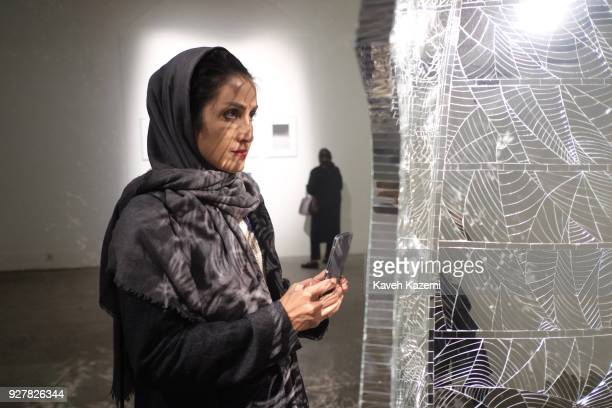 A veiled female takes a snap photo with her smartphone lin front of a work displayed in a group exhibition in Dastan Gallery on March 3 2017 in...