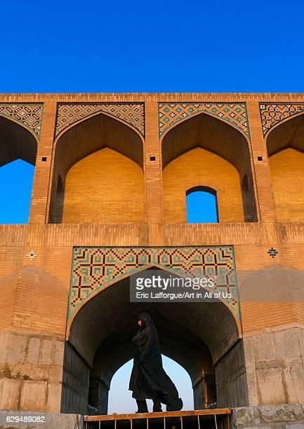 Veiled iranian woman passing in front of Khaju bridge Pol-e Khaju, Isfahan Province, Isfahan, Iran on October 13, 2016 in Isfahan, Iran.