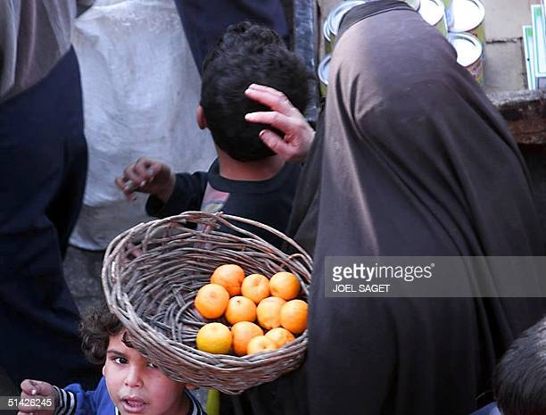 Veiled Iraqi woman and her children, shop in a Baghdad market 12 January. Iraq insisted 12 January on a total lifting of a 1990 UN embargo and said...