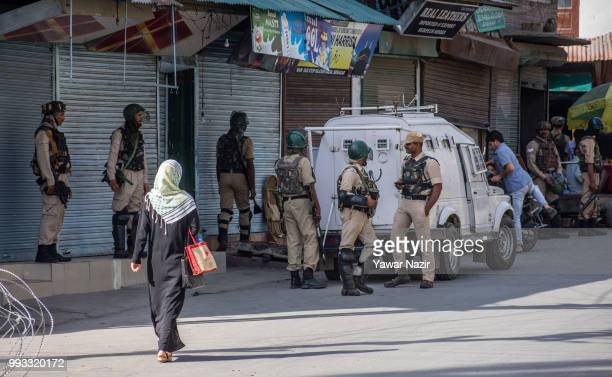 A veiled kashmiri Muslim woman walks in front of Indian government forces standing alert during a strike on July 8 2018 in Srinagar the summer...
